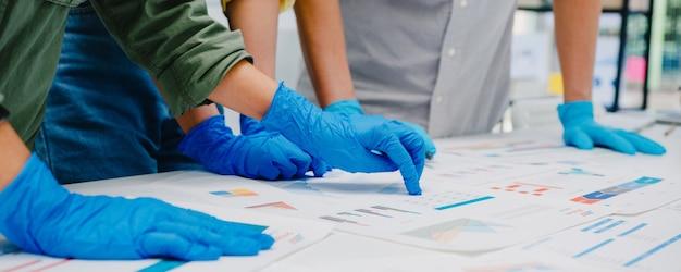 Aziatische ondernemers bespreken zakelijke brainstormvergadering samen delen gegevens, dragen gezichtsmasker en handschoen weer aan het werk in een nieuw normaal kantoor. levensstijl en sociale afstand nemen na het coronavirus.