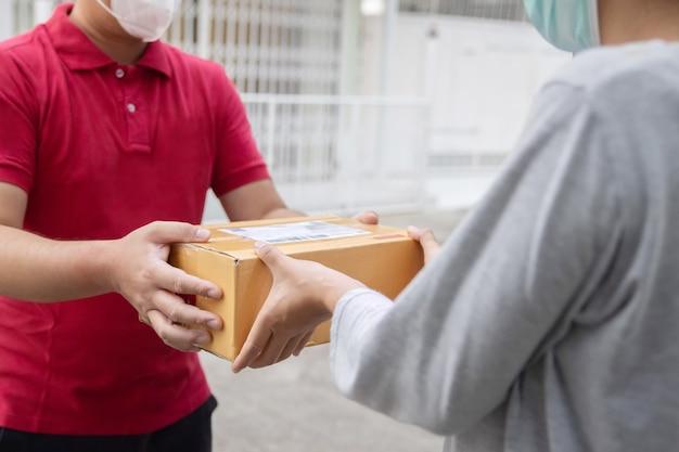 Aziatische online winkelbezorger met gezichtsmasker draagt een pakket bij de klant