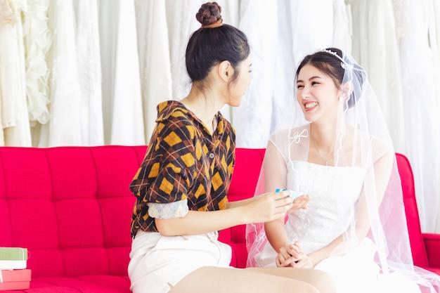 Aziatische ontwerper die in de opslagwinkel van de huwelijksmode werkt