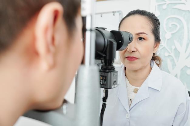 Aziatische optometrist die de patiënt onderzoekt