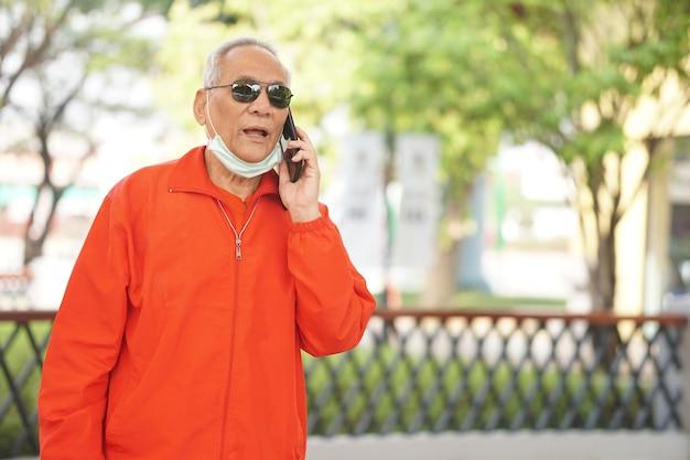 Aziatische oude aziatische oudere senior oudere man praten over slimme mobiele telefoon buiten