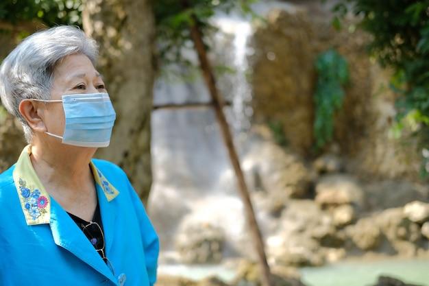 Aziatische oude bejaarde vrouwelijke oudere vrouw die gezichtsmasker draagt dat het ontspannen in tuin rust. senior vrije levensstijl