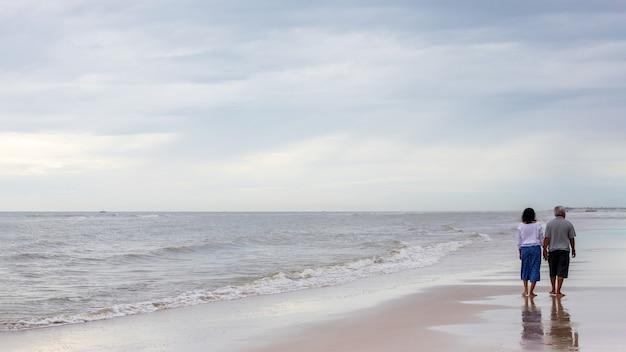 Aziatische oude hogere paren die bij het strand lopen