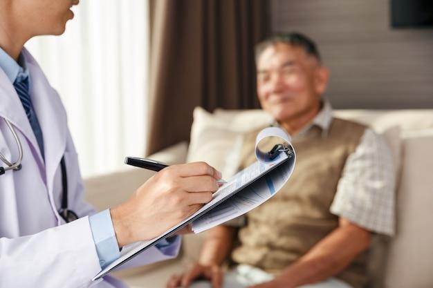 Aziatische oude man heeft doktersvergadering in de kliniek