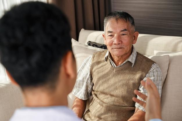 Aziatische oude man heeft doktersvergadering in de tuin