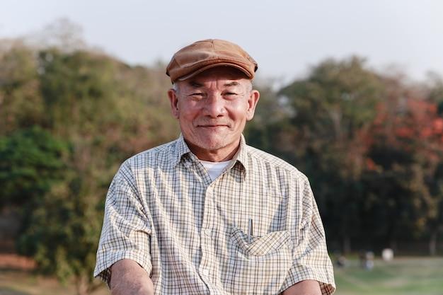 Aziatische oude man zitten en ontspannen in openbaar park.