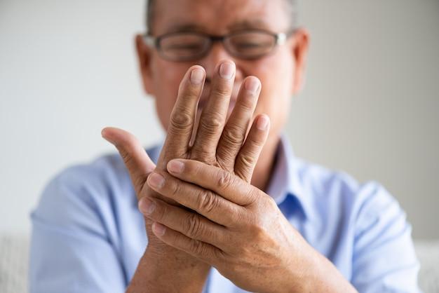 Aziatische oude mensenzitting op bank en het hebben van handpijn