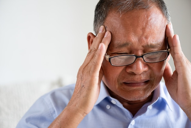 Aziatische oude mensenzitting op bank en thuis het hebben van hoofdpijn