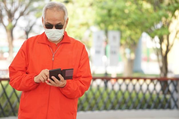 Aziatische oude oudere senior man bejaarde man dragen gezichtsmasker met behulp van mobiele smart phone cellphone buiten