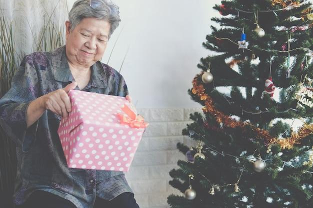 Aziatische oude oudere vrouw bejaarde senior vrouwelijke bedrijf geschenkdoos in de buurt van kerstboom