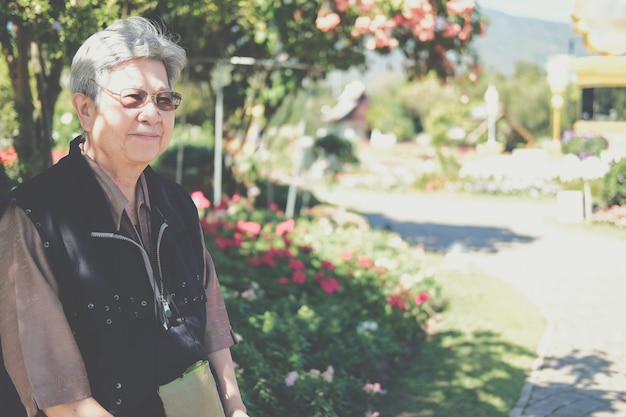 Aziatische oude oudere vrouwelijke oudere vrouw rust ontspannen in de tuin. senior vrije levensstijl