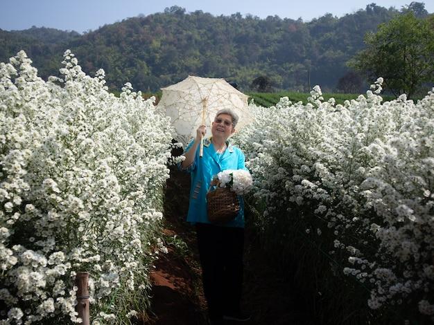 Aziatische oude oudere vrouwelijke oudere vrouw rusten ontspannen in bloementuin. senior vrije levensstijl