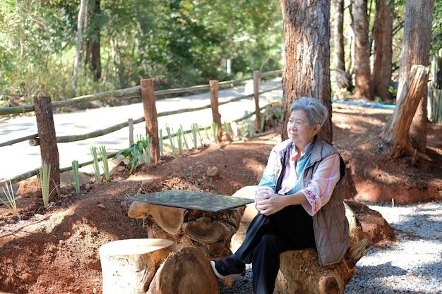 Aziatische oude oudere vrouwelijke oudere vrouw rusten ontspannen in park. senior vrije levensstijl