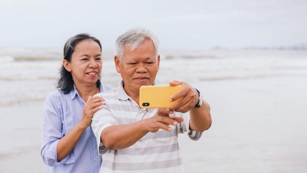 Aziatische oude senior stellen gebruiken smartphone voor selfie op het strand aan zee