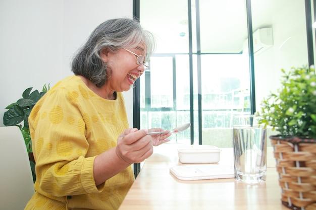 Aziatische oude vrouw blijft thuis tijdens de coronavirusepidemie eet ze graag. concept van preventie van infectie met het covid-19-virus.