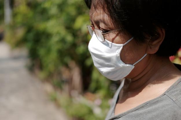 Aziatische oude vrouw die een bril en een wit stoffen masker draagt om het covid-19- of corona-virus in thailand te voorkomen en te beschermen tegen luchtvervuilingswaarde pm 2.5
