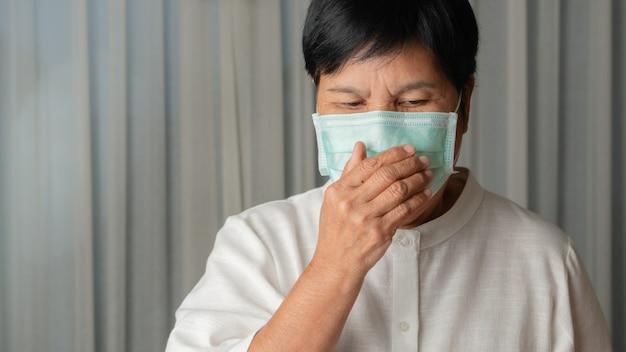Aziatische oude vrouw die een gezichtsmasker binnen hoesten draagt