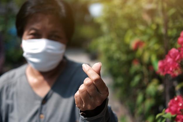 Aziatische oude vrouw die een wit stoffen masker draagt om het covid-19- of corona-virus te voorkomen