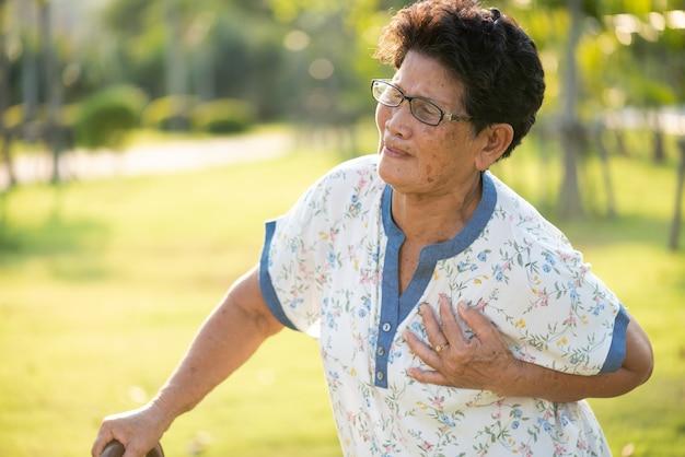 Aziatische oude vrouw die in park loopt en a met pijn op hart heeft