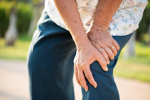 Aziatische oude vrouw die in park loopt en kniepijn heeft, knieverwonding in park