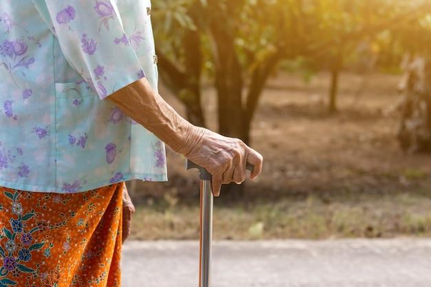 Aziatische oude vrouw die zich met haar hand op een wandelstok bevindt