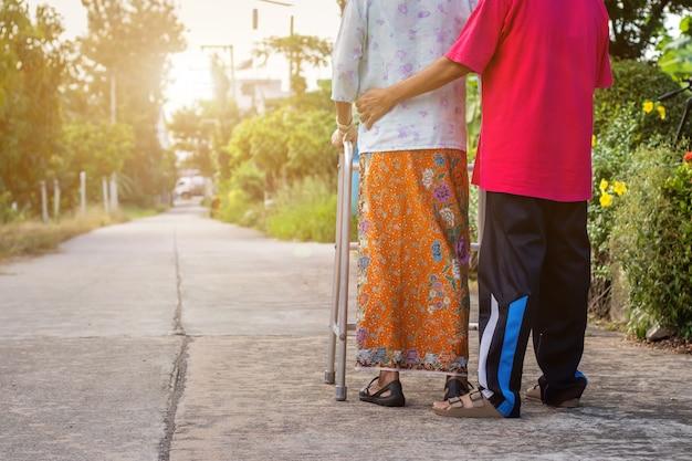 Aziatische oude vrouw die zich met haar handen op een rollator met de hand van de dochter bevindt