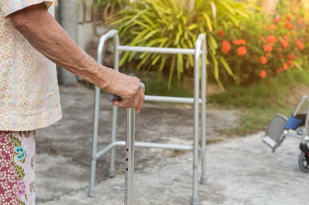 Aziatische oude vrouw die zich met zijn handen op een wandelstok bevindt