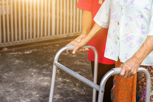 Aziatische oude vrouw stond met haar hand op een rollator met de hand van de dochter