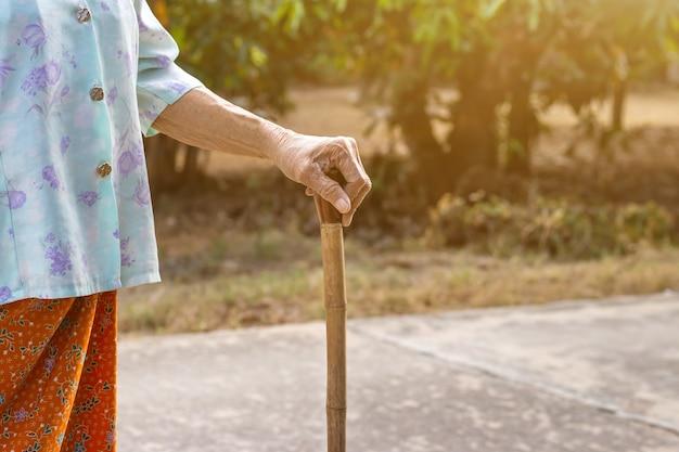 Aziatische oude vrouw stond met haar handen op een wandelstok, hand van oude vrouw met een stok van bamboe stok om te helpen lopen