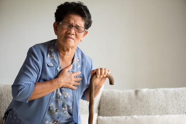 Aziatische oude vrouwenzitting op bank en het hebben van a met pijn op hart