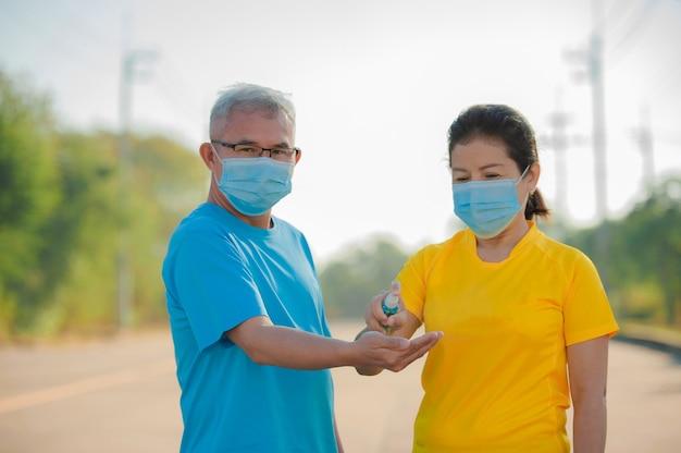 Aziatische oudere echtpaar dragen gezichtsmasker gebruik alcohol gel voor het reinigen van de hand te beschermen coronavirus covid 19, senior man vrouw oude verzekering