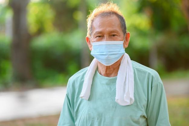 Aziatische oudere man of senior man een medisch masker dragen preventie van virussen en ziekte bij buitenactiviteiten en wandelen in het park.