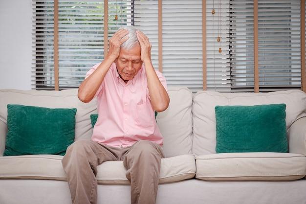 Aziatische oudere mannen hebben hoofdpijn geaccumuleerde stress door binnenshuis te zijn tijdens het coronavirus 2019.