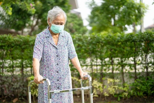 Aziatische oudere of oudere oude dame loopt met rollator en draagt een gezichtsmasker om het coronavirus covid19-virus te beschermen protect