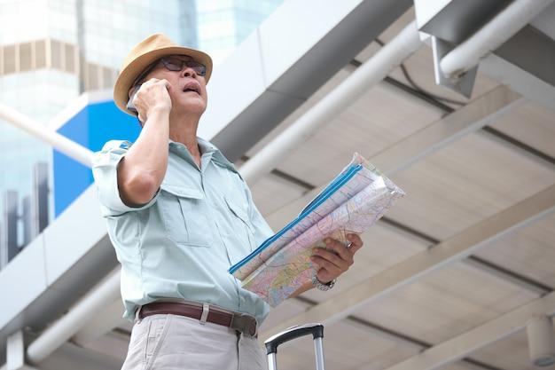Aziatische oudere toerist houdt een kaart vast en gebruikt een mobiele telefoon die de weg vraagt naar het hotel.