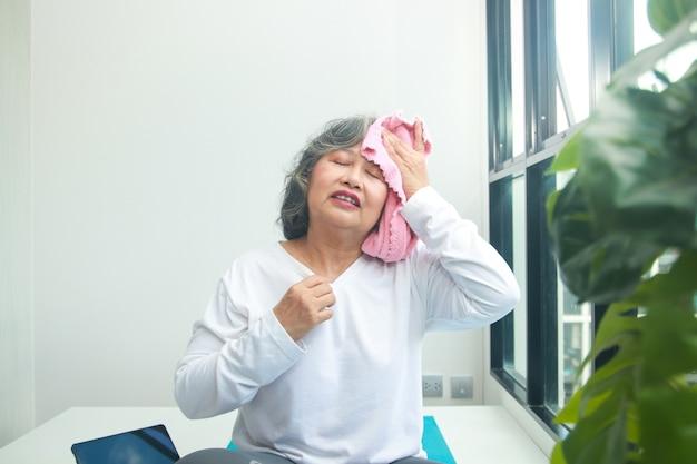 Aziatische oudere vrouw die thuis traint neem een roze doek om het zweet af te vegen. oefeningen om de gezondheid van ouderen te behouden. concept van sociale afstand