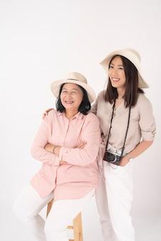 Aziatische oudere vrouw en haar dochter op witte muur, reisconcept