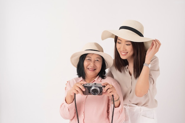Aziatische oudere vrouw en haar dochter op witte muur