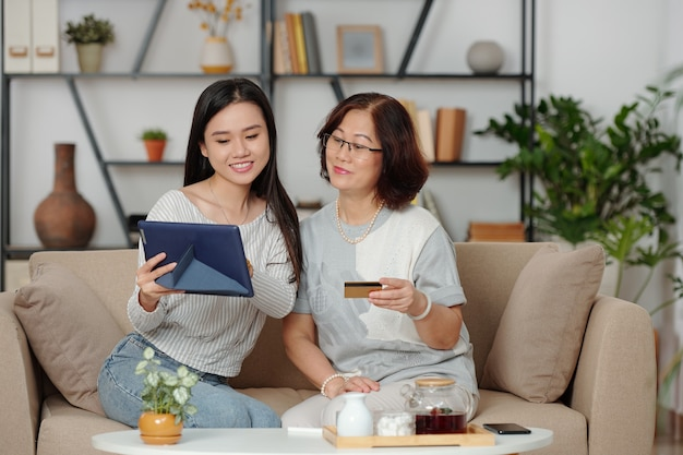 Aziatische oudere vrouw en haar volwassen dochter die samen online winkelen als ze samen een weekend thuis doorbrengen