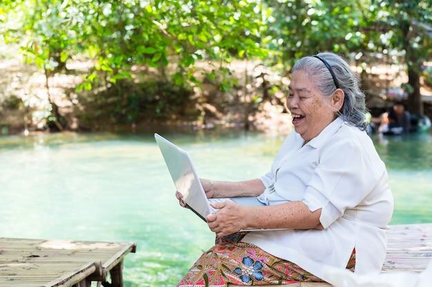 Aziatische oudere vrouw geniet met laptop
