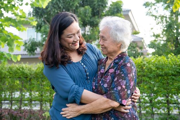 Aziatische oudere vrouw met hulp bij het lopen van de verzorger met liefde en gelukkig in het natuurpark.