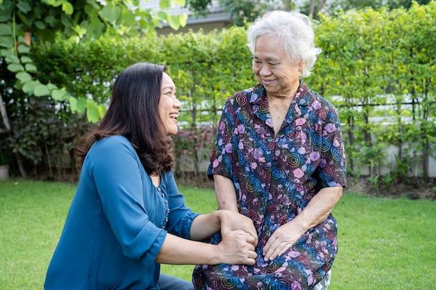 Aziatische oudere vrouw met verzorger geniet en is gelukkig in het natuurpark.