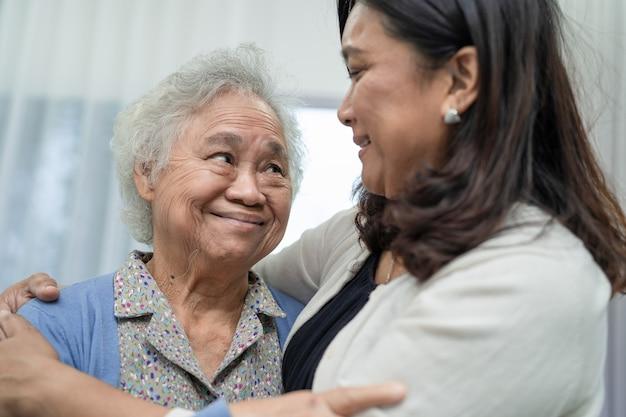 Aziatische oudere vrouw met verzorger wandelen met gelukkig.
