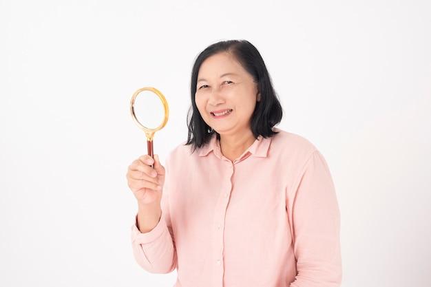 Aziatische oudere vrouw op witte muur