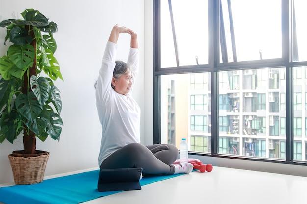 Aziatische oudere vrouw zit thuis aan oefeningen doe yogahoudingen volgens een online fitnessleraar via videogesprek via tablet. social distancing, behoud van de gezondheid van ouderen