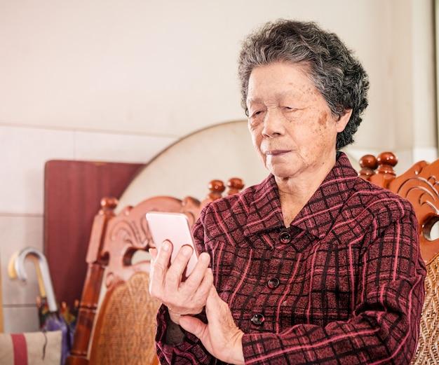 Aziatische oudere vrouw zitten en kijken op smartphone