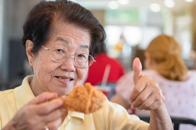 Aziatische oudere vrouwen eten gefrituurde kip. in het restaurant en til de duim op.