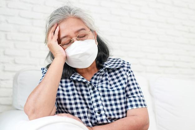 Aziatische oudere vrouwen met maskers ze voelde zich duizelig en had griep. ga thuis op de bank zitten. thuis voor jezelf zorgen tijdens de covid-19 pandemie. zelfzorg om besmetting met het coronavirus te voorkomen