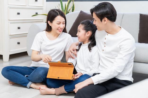Aziatische ouders begeleiden hun dochter bij het gebruik van de tablet