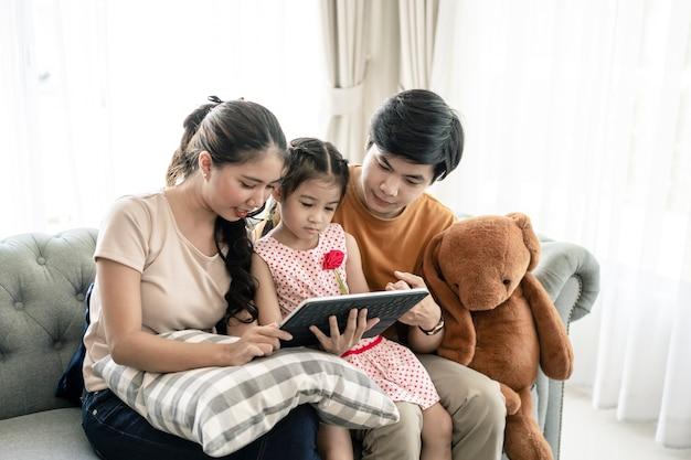 Aziatische ouders en een jong geitjekind bekijken laptop thuis. familie concept.